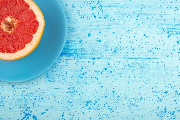 Vista superior rodajas de pomelo jugoso suave en la placa azul y piso azul brillante Foto gratis