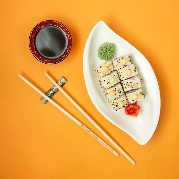 Vista superior de rollos de sushi servidos con salsa de soja, wasabi y jengibre Foto gratis