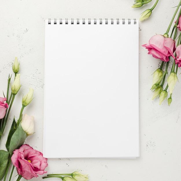 Vista superior rosas al lado del cuaderno Foto gratis