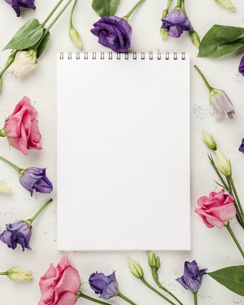 Vista superior rosas coloridas al lado del cuaderno Foto gratis