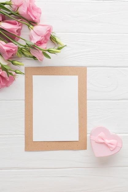 Vista superior de rosas rosadas con pequeña caja de regalo Foto gratis