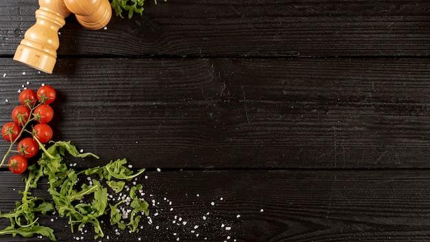 Vista superior de rúcula y tomates con espacio de copia Foto gratis