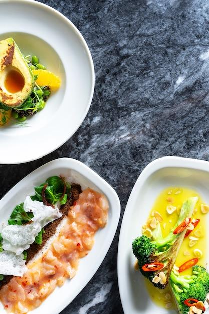 Vista superior de sabrosa comida de lujo con estilo de comida de restaurante en la mesa de mármol. ensaladas de verduras frescas y asadas con ceviche de aguacate, brócoli y lubina en plato blanco. Foto Premium