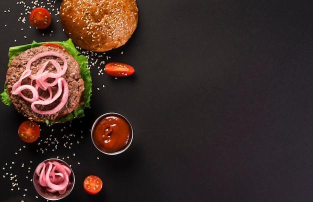Vista superior sabrosa hamburguesa de ternera con salsa de salsa de tomate Foto gratis