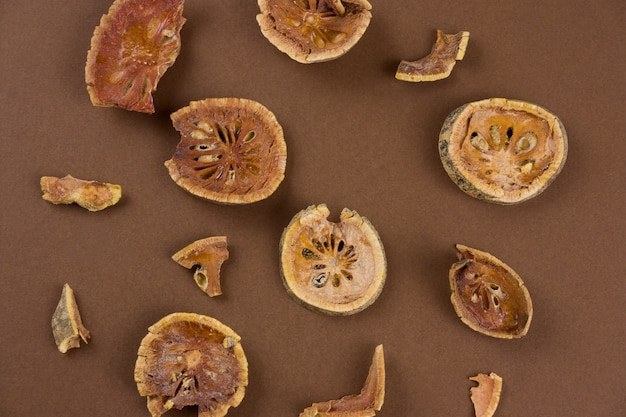 Vista superior secada rebanadas de fruta bael (matum) sobre un fondo marrón Foto Premium