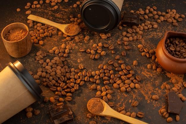 Una vista superior de semillas de café marrón con barras de chocolate y tazas de café Foto gratis