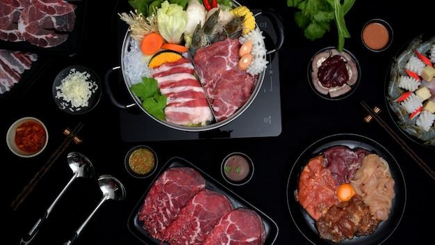 Vista superior de shabu-shabu en olla caliente, carne fresca en rodajas, mariscos, verduras y salsa de fondo negro Foto Premium
