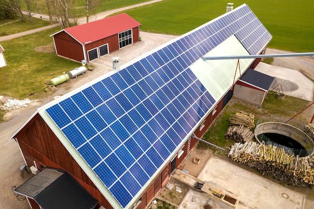 Vista superior del sistema de paneles fotovoltaicos solares azules en el edificio de madera, granero o techo de la casa. producción ecológica renovable de energía verde. Foto Premium