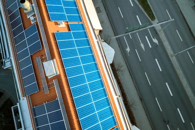 Vista superior del sistema de paneles fotovoltaicos solares de color azul en la parte superior de la azotea del edificio de apartamentos en un día soleado. producción ecológica renovable de energía verde. Foto Premium