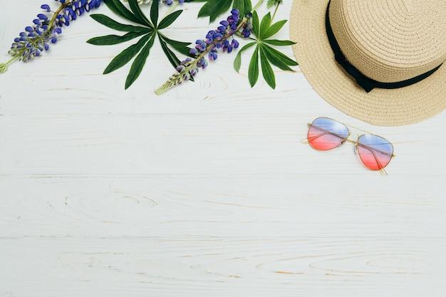 Vista superior, sombrero de paja, gafas de sol y flores sobre un fondo blanco Foto Premium