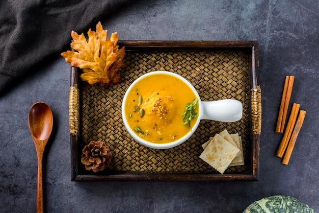 Vista superior de sopa de calabaza en bandeja de madera Foto gratis