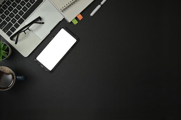 Vista superior de suministros de oficina con bloc de notas, computadora portátil y taza de café Foto Premium