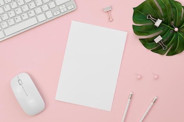 Vista superior de suministros de oficina con teclado vegetal Foto gratis