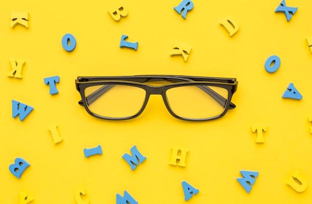 Vista superior de los suministros de regreso a la escuela con gafas y letras Foto gratis