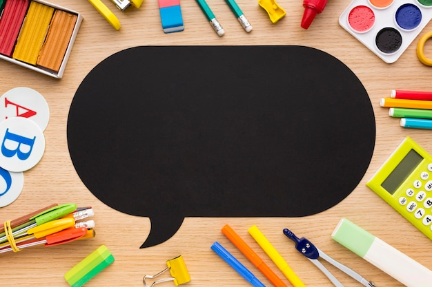 Vista superior de suministros para el regreso a la escuela con lápices y burbuja de chat Foto gratis