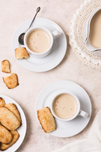 Vista superior surtido de café y leche con merienda Foto gratis
