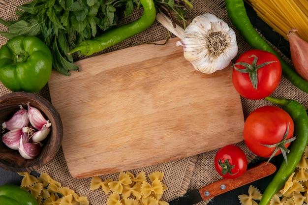 Vista superior de la tabla de cortar con tomates campana de ajo y pimientos picantes y cebollas con menta en una servilleta beige Foto gratis