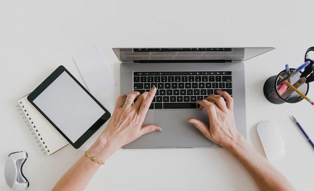 Vista superior de la tableta de maqueta y la persona escribiendo en la computadora portátil Foto gratis
