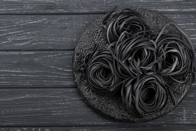 Vista superior de tagliatelle negro en placa Foto gratis