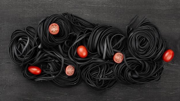 Vista superior de tagliatelle negro con tomate Foto gratis