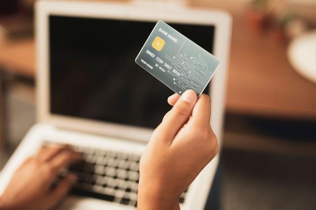 Vista superior de la tarjeta de crédito en la mano con portátil borrosa en el fondo Foto gratis
