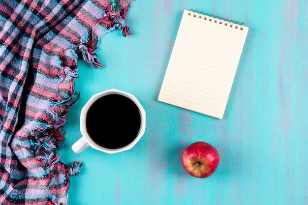 Vista superior taza de café con cuaderno y manzana roja sobre mesa azul Foto gratis