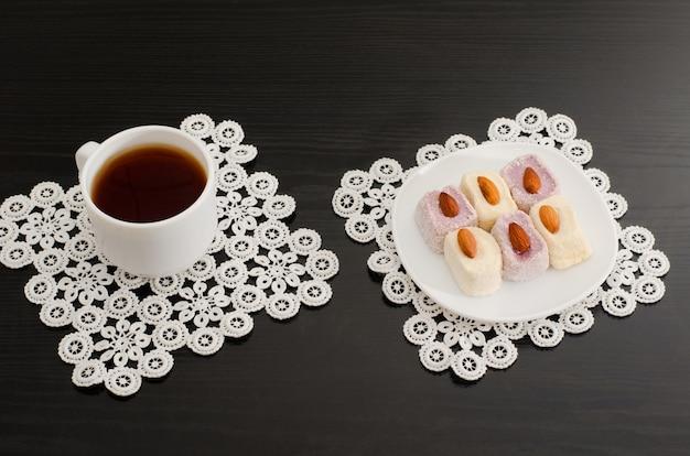 Vista superior de una taza de café y delicias turcas coloridas con almendras en las servilletas de encaje mesa negra Foto Premium