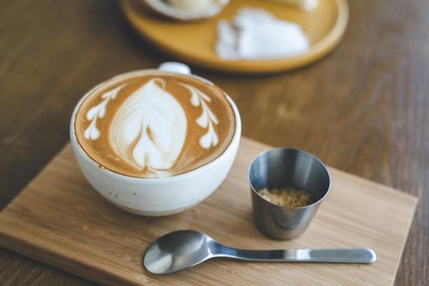 Vista superior de una taza de café con leche en la cafetería de café en el tablero de madera Foto Premium