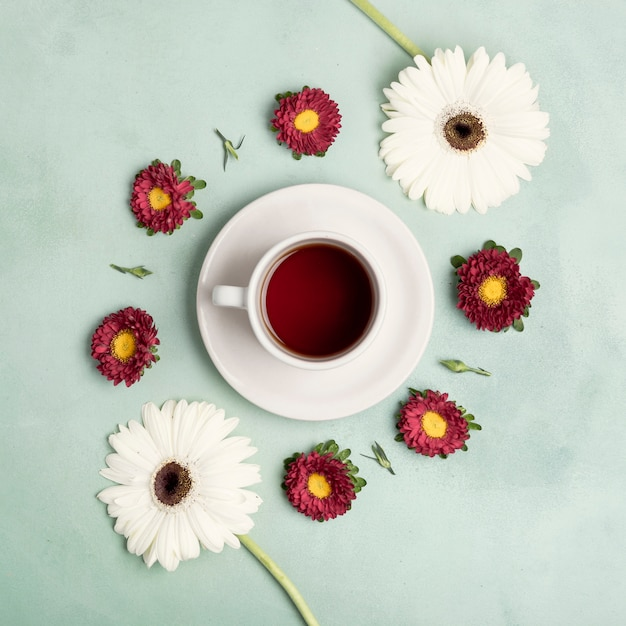 Vista superior taza de té de frutas y arreglo de margaritas Foto gratis
