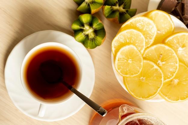 Vista superior taza de té con frutas sobre fondo liso Foto gratis