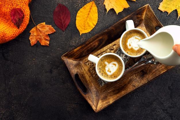 Vista superior de tazas de café alrededor de hojas amarillas Foto Premium