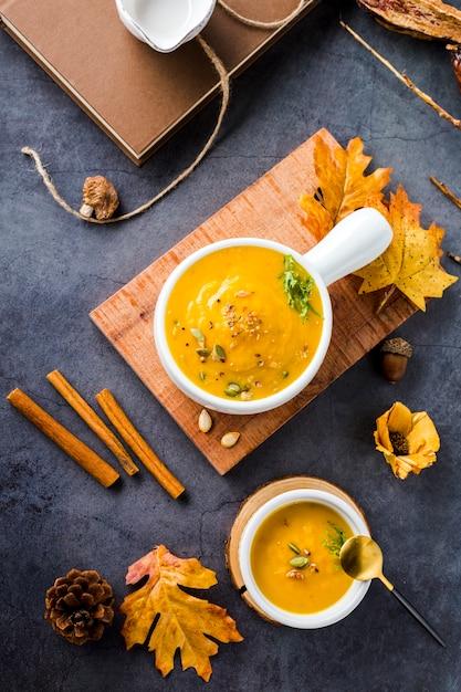 Vista superior de los tazones de sopa de calabaza en tabla de madera Foto gratis
