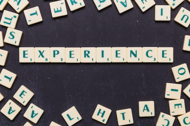 Vista superior del texto de la experiencia con letras scrabble sobre fondo negro Foto gratis