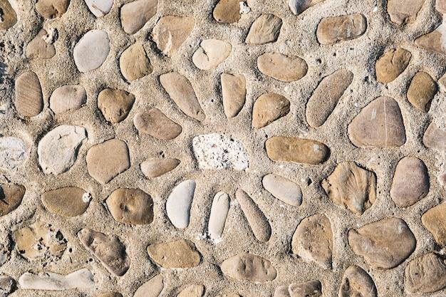 Vista superior de la textura del piso de la calle del guijarro con el ornamento del sol. Foto Premium