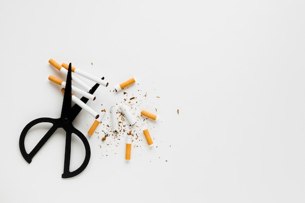 Vista superior tijeras con cigarros Foto gratis