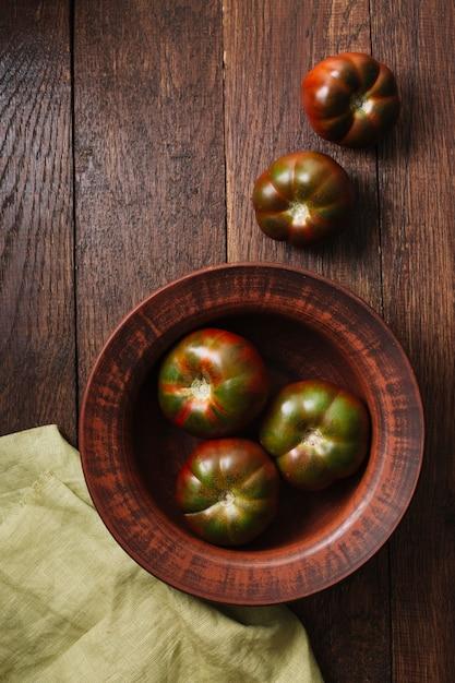 Vista superior de tomates en un tazón y tela Foto gratis