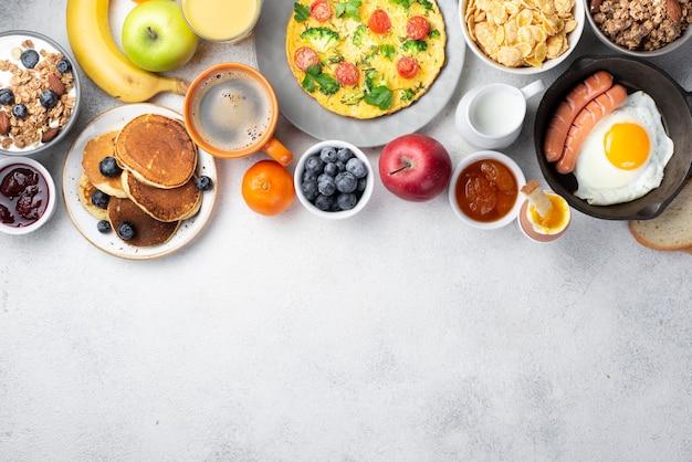 Vista superior de tortilla con huevo y salchichas y variedad de alimentos para el desayuno. Foto Premium