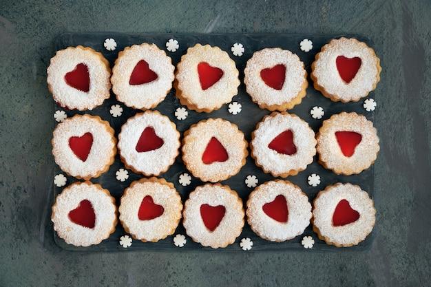 Vista superior de las tradicionales galletas linzer de navidad con mermelada roja en la oscuridad Foto Premium