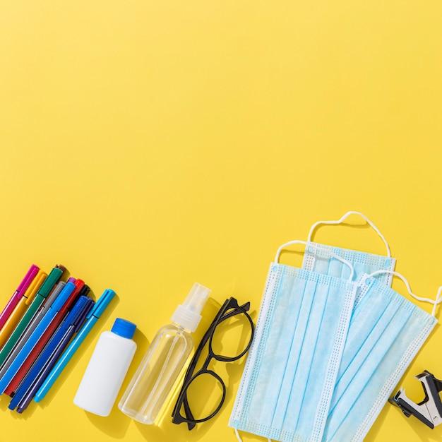 Vista superior de útiles escolares con lápices y desinfectante para manos Foto gratis