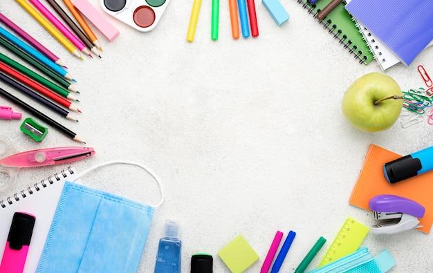 Vista superior de útiles escolares para el regreso a la escuela con lápices y manzana Foto gratis