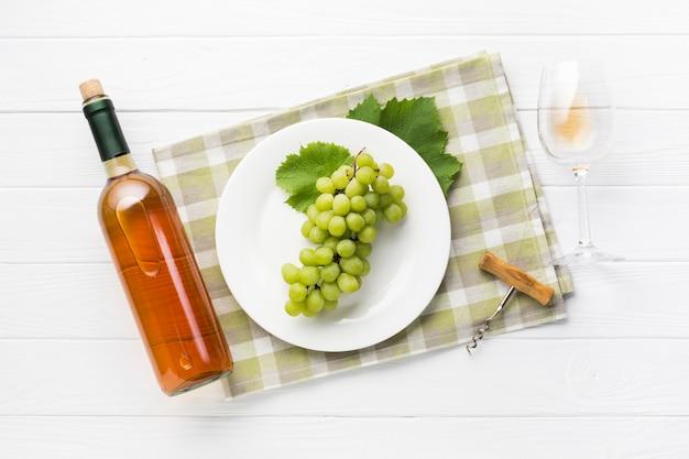 Vista superior de uvas blancas y vino. Foto gratis