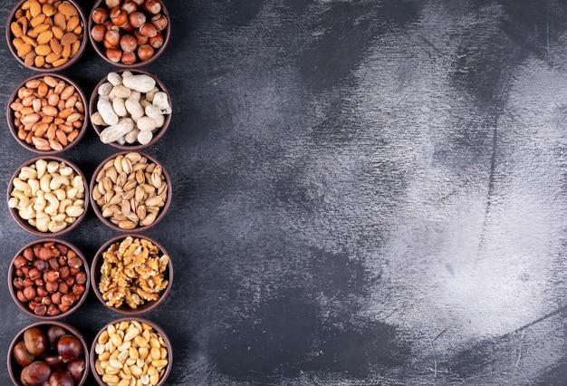 Vista superior de una variedad de nueces y frutas secas en mini tazones diferentes con nueces, pistachos, almendras, maní Foto gratis