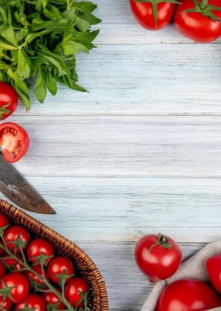 Vista superior de verduras como tomate hojas de menta verde con cuchillo en superficie de madera con espacio de copia Foto gratis