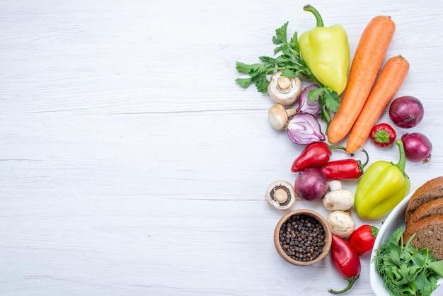 Vista superior de verduras frescas como pimiento, zanahoria, cebollas con pan en la mesa de luz, comida vegetal, vitamina Foto gratis