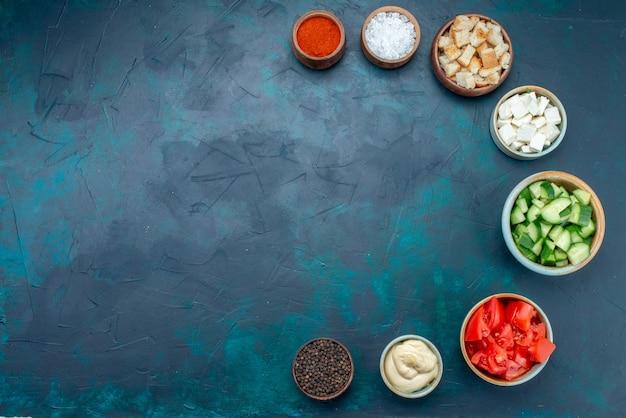 Vista superior de verduras en rodajas con condimentos en el color de ensalada de verduras de fondo azul oscuro Foto gratis