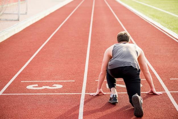 Vista trasera del atleta masculino listo para comenzar la carrera de relevos en la pista de atletismo Foto gratis
