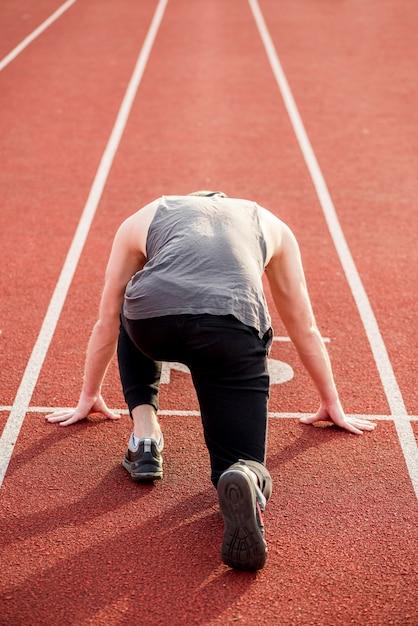 Vista trasera de un atleta masculino tomando posición en la pista roja para correr Foto gratis