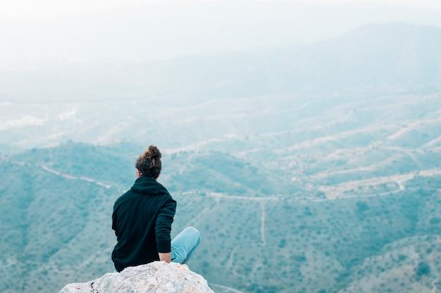 Vista trasera de un excursionista masculino sentado en la cima de la roca con vistas a la montaña Foto gratis
