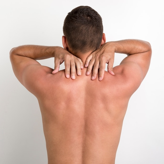 Vista trasera del hombre sin camisa con dolor de espalda de pie contra la pared blanca Foto gratis