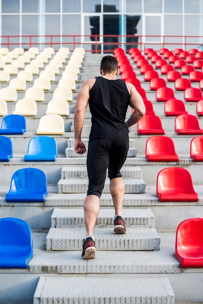 Vista trasera de un hombre corriendo escaleras arriba en la grada Foto gratis
